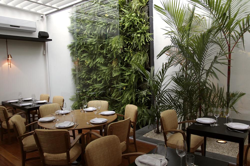 O salão do fundo, regado à luz natural com vista para um jardim vertical (Fonte: Alcance Construtora)