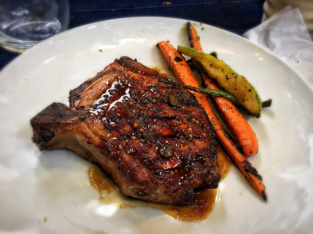 Bisteca alta de porco com legumes na brasa e molho charcutiére.