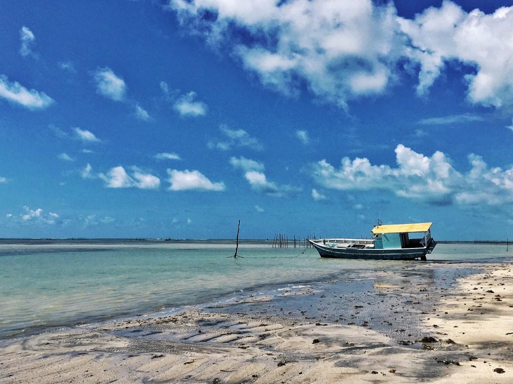 Barquinho preso na areia com a maré baixa